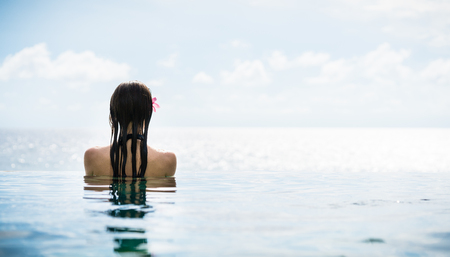 Woman tourist in infinity pool of hotel resort enjoying the view over the ocean Stock Photo