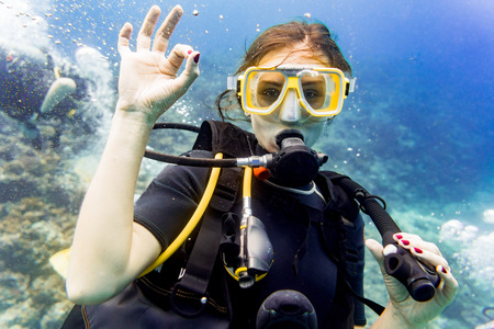 scuba woman: Woman diving in her vacation on coral reef giving the ok sign Stock Photo