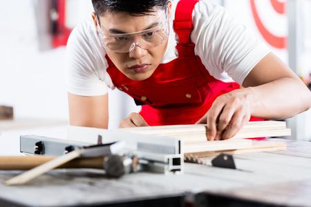 circular saw: Asian Chinese Carpenter cutting wood with circular saw in his workshop