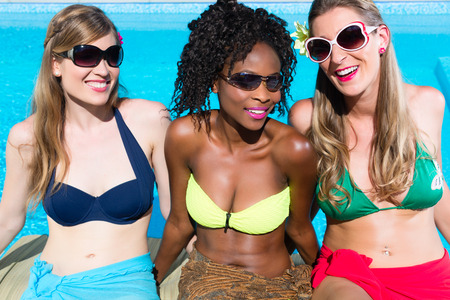 pretty black woman: Three girls sitting on swimming pool in summer relaxing, African and Caucasian girls
