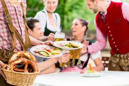beer garden: Waiter serving food in Bavarian beer garden, people eating and drinking in background