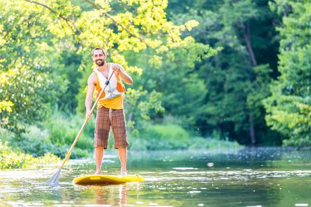 Man peddelen op SUP in de rivier