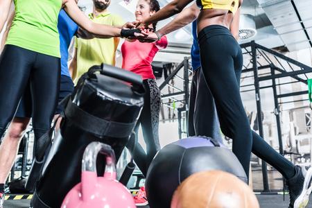 Vrouwen en mannen die gemotiveerd voor fitness en sport stapelen hun handen