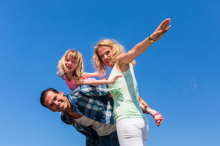 confidence: Father, mother and daughter playing plane Stock Photo