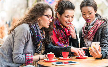 drink coffee: Multicultural group of women in cafe showing each other pictures on smart phone and chatting