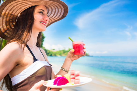 water melon: woman tourist at tropical beach eating fruit like water melon, pineapple and barbary fig for breakfast Stock Photo