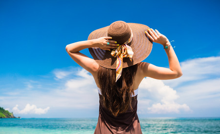 woman back view: Woman in summer vacation wearing straw hat and beach dress enjoying the view at the ocean