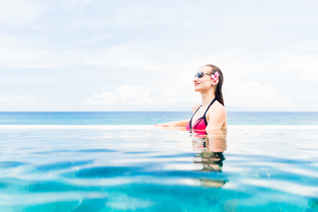 view on sea: Woman wearing red bikini and flower in hair in infinity Pool with ocean in the background