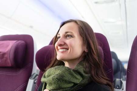 air travel: Happy woman with green scarf during flight in airplane Stock Photo