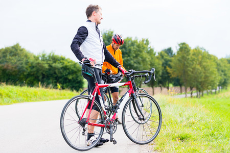 healthy path: Two sport cyclists, descended, having a break
