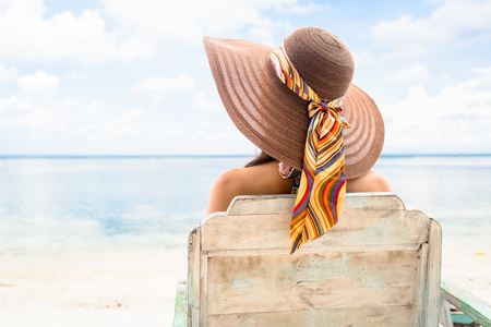 Female tourist relaxing in deck chair at beach in vacation