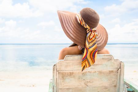 Vrouwelijke toerist ontspannen in ligstoel op het strand in de vakantie Stockfoto