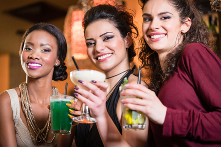 Beautiful girls in nightlife drinking cocktails and saying Cheers