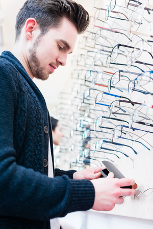 optician: Man as customer choosing glasses from shelf in optician shop