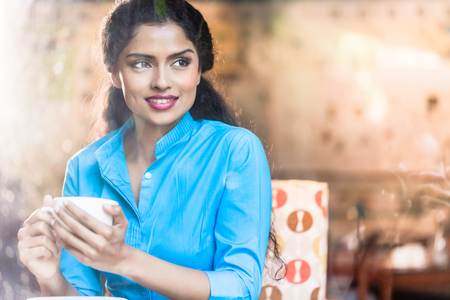 flirty: Indian woman with coffee mug and flirty expression