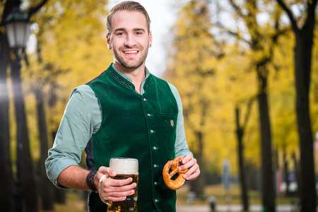 tracht: Bavarian man in traditional Tracht drinking beer out of a huge mug, holding pretzel in other hand