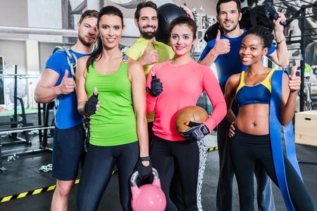 Groep van vrouwen en mannen in de sportschool die zich voordeed op fitness training staan samen met spullen en halters