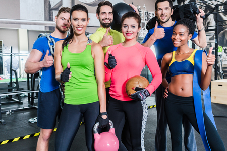 functional: Group of women and men in gym posing at fitness training standing together with gear and dumbbells