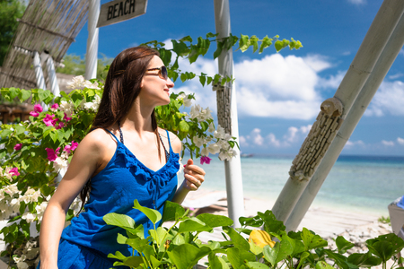 Woman with sunglasses sitting in garden near the sea