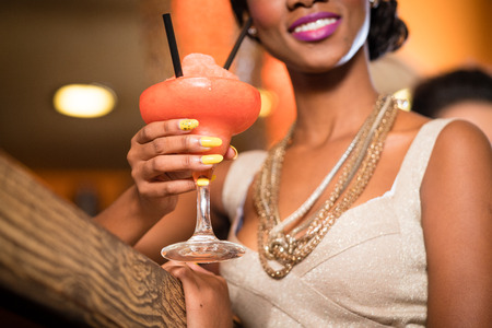 African Woman with golden necklaces in a bar drinking frozen daiquiri