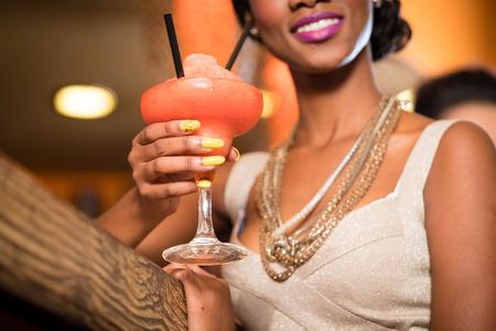 margarita cóctel: Mujer africana con collares de oro en un bar bebiendo daiquiri congelado