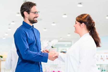 drug store: Man in drug store with sales lady shopping, woman and man doing handshake Stock Photo
