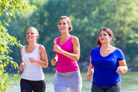 湖畔のジョギングで走っている女性のグループ 写真素材