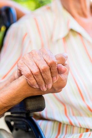 wheel chair: Nurse holding hand of senior woman in wheel chair