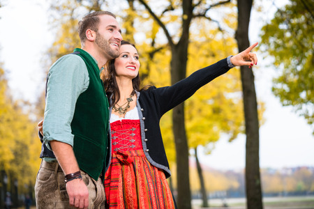 tracht: Happy woman and man in Tracht having a walk, girl pointing at something Stock Photo
