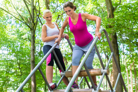 balancing act: Two women, one pregnant, at fitness sport in climbing park