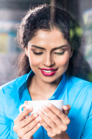 Indian woman with coffee mug and flirty expression