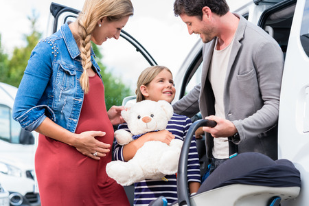 soft toy: Family buying car, mother, father and child at dealership with soft toy and special kid seat