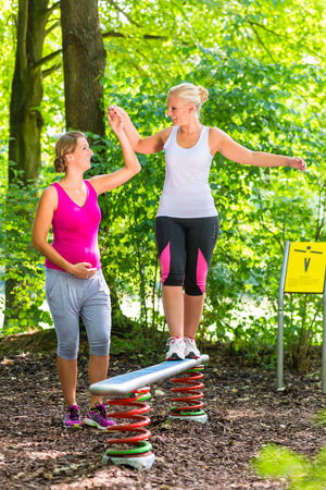 balancing act: Woman balances getting help from pregnant training partner Stock Photo