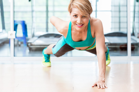 one armed: Frontal view of smiling young woman doing one arm pushup in gym Stock Photo