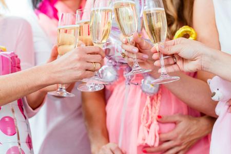 Amigos que tintinean los vidrios de la fiesta de bienvenida al bebé, primer tiraron en el vino espumoso Foto de archivo - 62009935