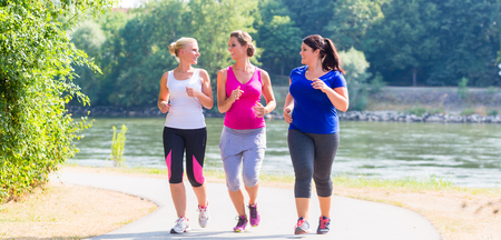 Group of women running at lakeside jogging Imagens - 63374335