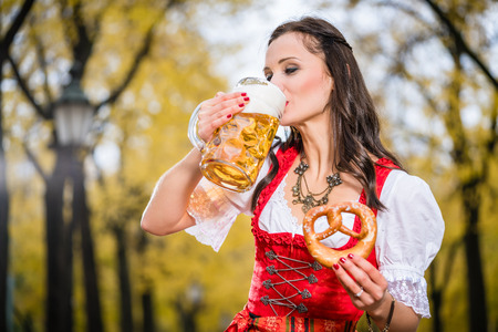 Girl in traditional Bavarian Tracht drinking beer out of a huge mug, holding pretzel in other hand Stock Photo