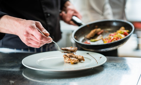 Chef finishing food on plate in restaurant or hotel kitchen Stock Photo