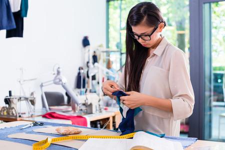 Aziatische modeontwerper vrouw opstelt gesneden patroon in haar atelier