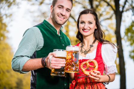 tracht: Bavarians in Tracht with Beer and Pretzel in autumn