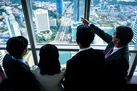 Group of Asian real estate business people looking at city skyline from skyscraper office building