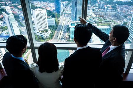 Grupo de hombres de negocios asiáticos de bienes raíces que mira horizonte de la ciudad desde el edificio de oficinas del rascacielos