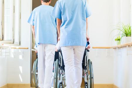 thru: Nurses pushing seniors in wheelchair thru nursing home