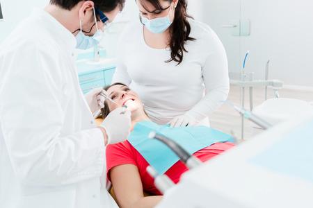 Zahnarzt und Sanitäter behandeln schwangere Frau Patient in ihrer Operation Standard-Bild - 61779235