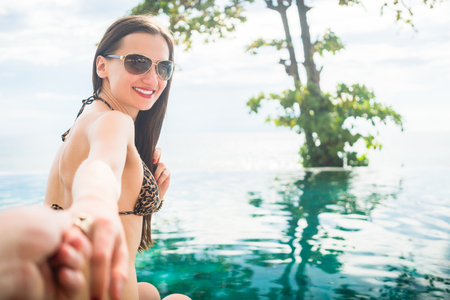 tempt: Woman in tropical vacation drags man along in swimming pool by the sea