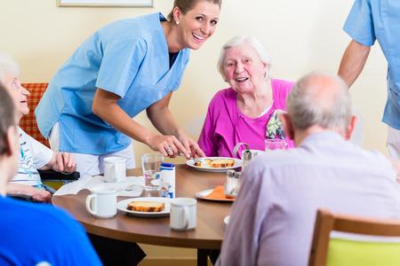 Grupo de personas mayores que tienen los alimentos en el hogar de ancianos, una enfermera está cumpliendo