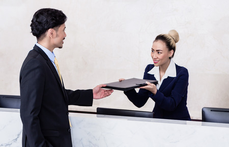 front desk: Job Applicant at business front desk giving his documents to receptionist