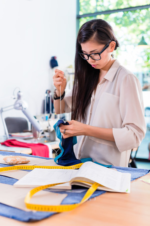 fashion: Asian fashion designer woman drafts cut pattern in her workshop Stock Photo