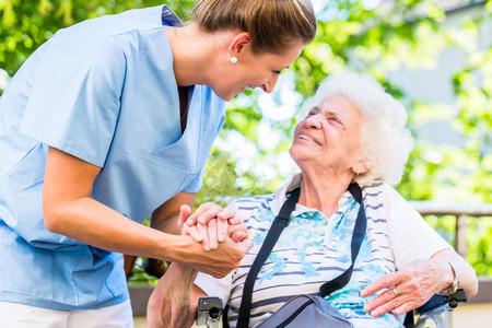 看護師年金ホームで年配の女性の手を握って 写真素材