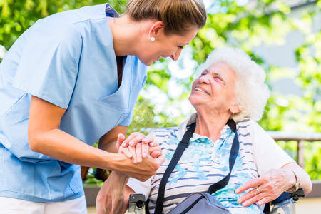 Sestra drží za ruku starší ženy v důchodovém doma